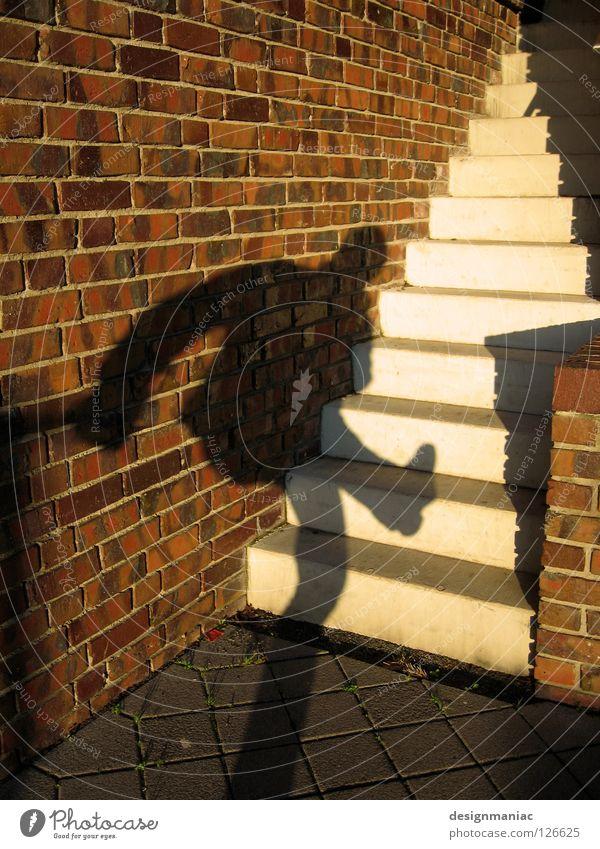 Schattendasein Wand Dieb Backstein Licht schwarz rot weiß Mauer Schlagschatten steigen Eingang Besucher Treppe Sonne aufwärts Beine oben hoch Stein
