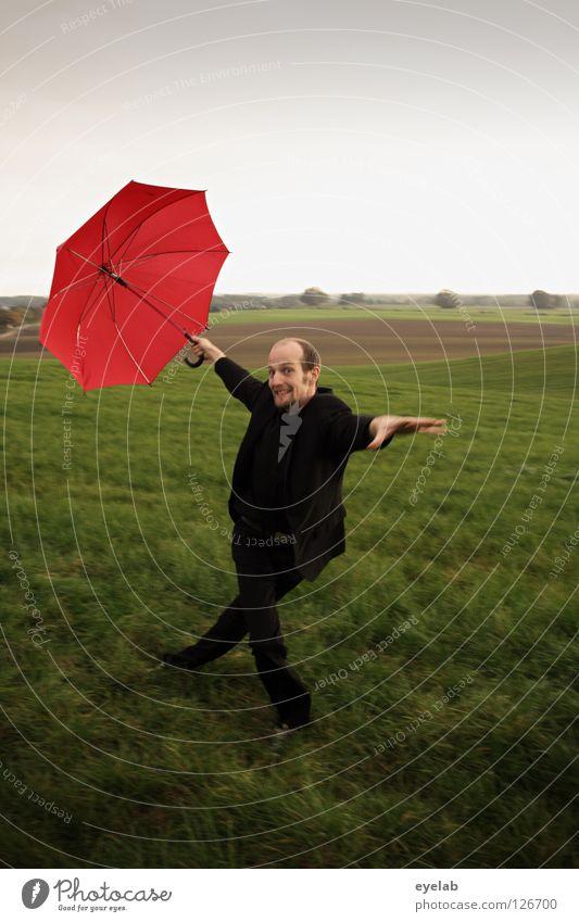 Eiernacken Mann Regenschirm Feld Landwirtschaft Wiese Ebene Anzug grün rot schwarz Kerl Grimasse Akrobatik Kunst Horizont Zirkus improvisieren Tanzen Spielen