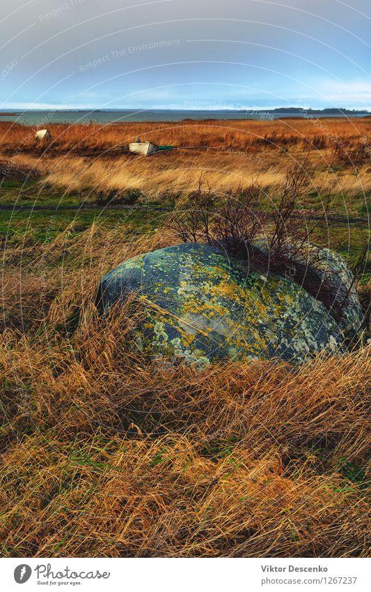 Ein halber Stein im gelben Gras und Boot gehackt Strand Meer Insel Seil Natur Landschaft Himmel Horizont Wind Felsen Küste See Wasserfahrzeug alt nah retro blau