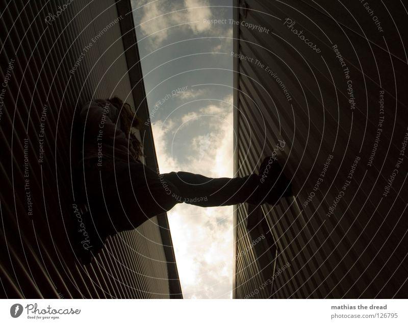 Kaminklettern Wand Fassade Blech Wellen Wellblech Fenster Froschperspektive Klettern Pause anstrengen Wolken Gasse parallel Mann dunkel kalt gefährlich