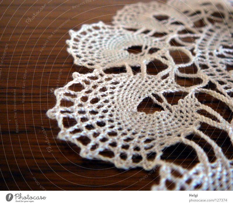 Nahaufnahme eines gehäkelten Spitzendeckchens auf einem Tisch Decke Handwerk anstrengen Nähgarn flach rund krumm Freizeit & Hobby weiß braun Makroaufnahme