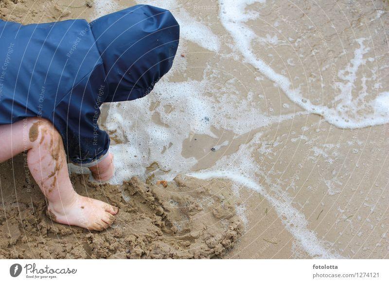 Buddeln Freude Spielen matschen Strand Kleinkind Beine Fuß Natur Sand Wasser Wellen Flussufer Regenjacke nass blau beige Matschepampe Barfuß Wind Außenaufnahme