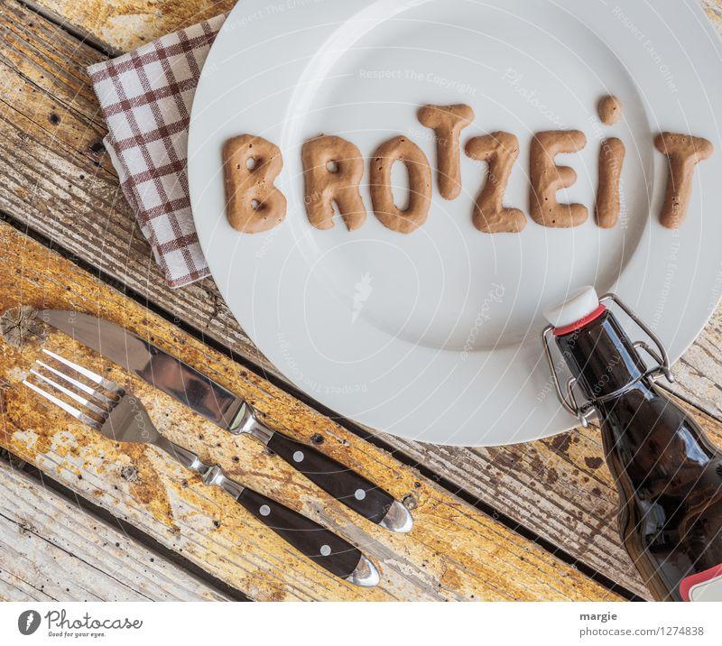 :Auf einem rustikalen Holztisch ein Teller mit den Buchstaben BROTZEIT, Messer und Gabel, Serviette und eine Flasche Bier Lebensmittel Brot Vesper Ernährung