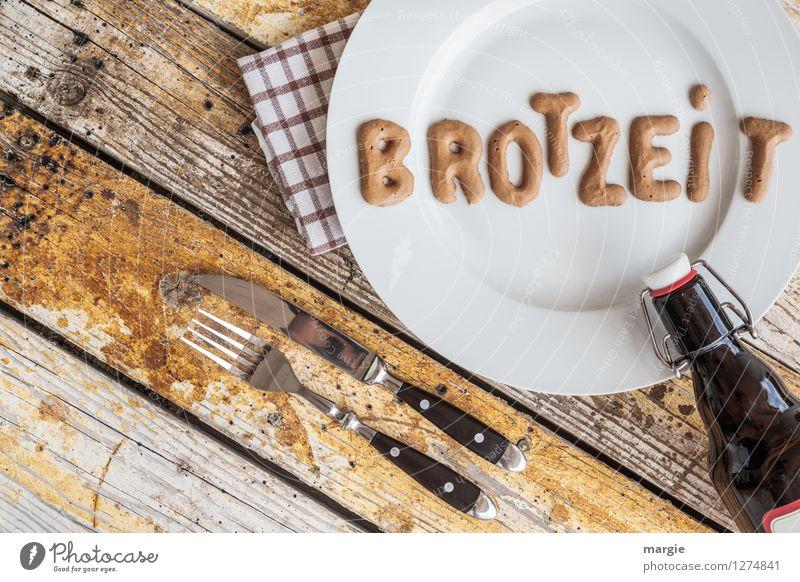 Auf einem rustikalen Holztisch ein Teller mit den Buchstaben BROTZEIT, Messer und Gabel, Serviette und eine Flasche Bier im Querformat Lebensmittel Brot