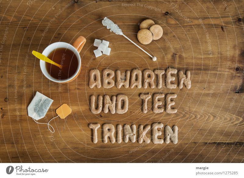 ABWARTEN UND TEE TRINKEN: eine Teetasse mit Teebeutel, Zucker und Plätzchen auf einem Holztisch Lebensmittel Dessert Süßwaren Getränk Heißgetränk Tasse Löffel