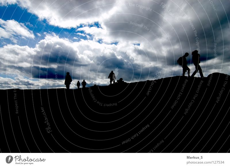 Kontraste Himmel blau schwarz Wolken Menschengruppe wandern Spaziergang
