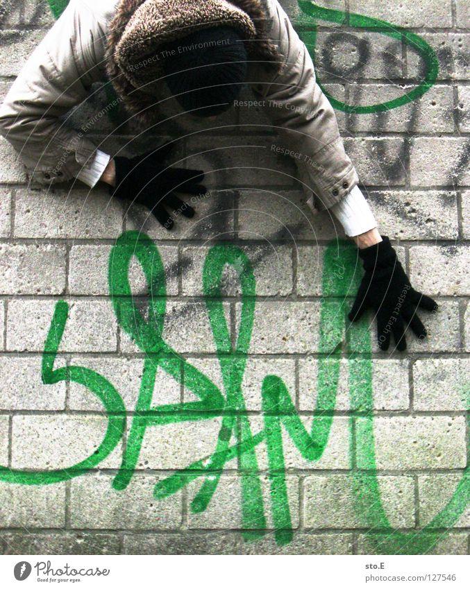 i spam you voll Kerl Mann Wand Mauer Glätte Spray Farbdose grün Aufschrift Wort E-Mail ungebeten nervig unabsichtlich hängen Mütze Handschuhe schwarz Jacke
