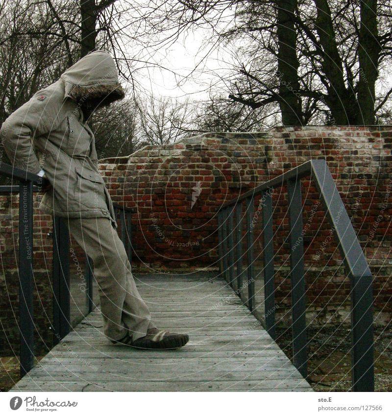last man standing Kerl Körperhaltung Steg Holz Wand Mauer Backstein verloren Verfall Baum Pflanze dunkel Sträucher Wald abstützen Mütze Jacke grau Osten