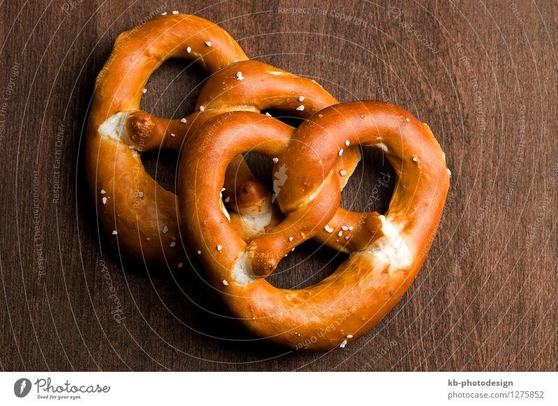 Bavarian pretzel on a brown background Lebensmittel Teigwaren Backwaren Ernährung Essen Oktoberfest München Deutschland Feste & Feiern eat cheers invitation