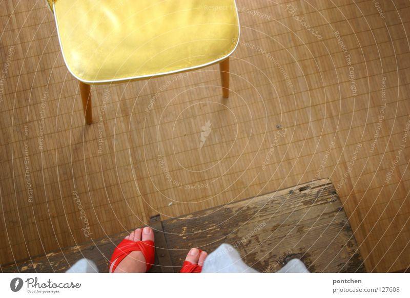 Frauenfüße in roten Sandalen stehen auf einer Holzkiste vor einem gelben Stuhl. Distanz, Entfernung, Höhe. Mit, Angst Vogelperspektive Spielen Kinderspiel Ferne