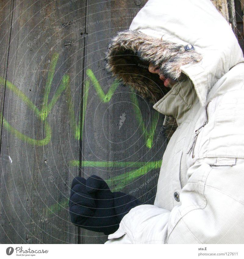 KMsto.E Kerl Körperhaltung Holz Eingang Wand Muster Holzbrett Aufschrift Schmiererei Kilometer Richtung Mütze Jacke grau Handschuhe schwarz Osten historisch