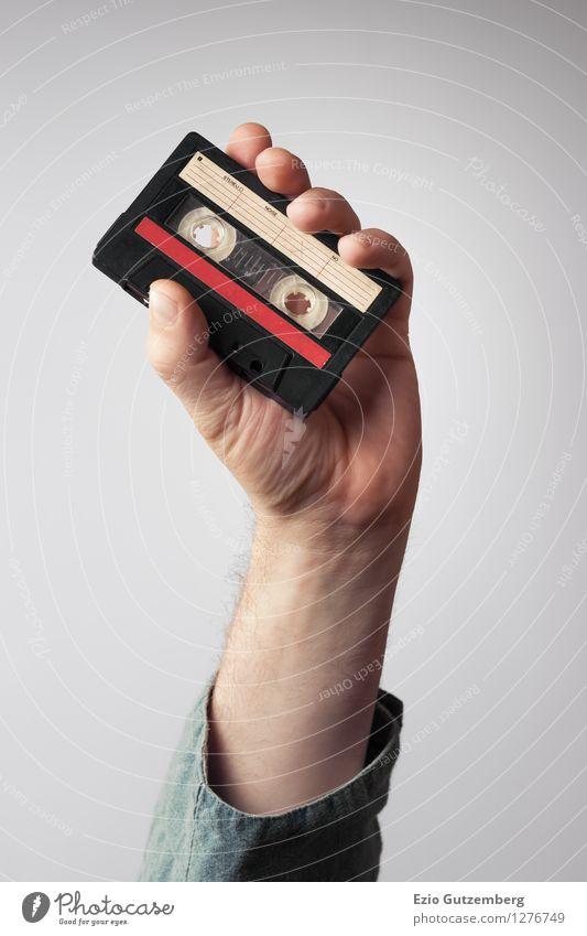 Hand hält eine Musikkasette aus den 80er Jahren in die Höhe Mensch Stadt schön Hand rot Freude schwarz Erwachsene Stil Lifestyle Mode Stimmung Party Design maskulin modern