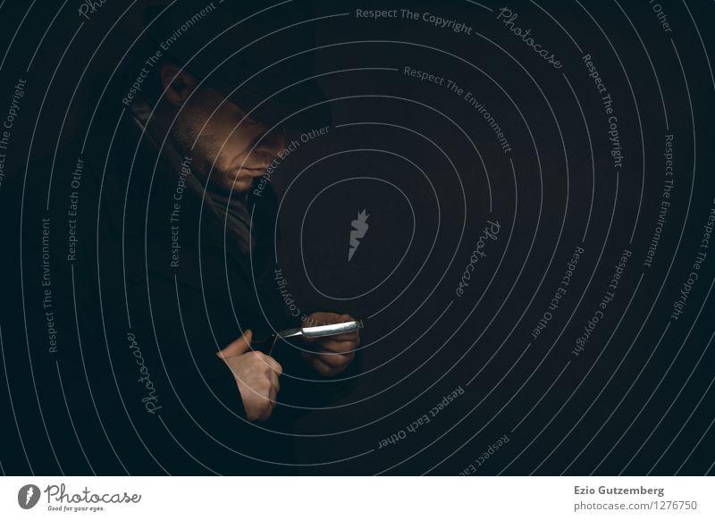Mann prüft sein Rasiermesser in der Dunkelheit Stil Körperpflege Mensch maskulin Gesicht Hand Finger 1 30-45 Jahre Erwachsene Mantel Schal Hut Zopf Bart