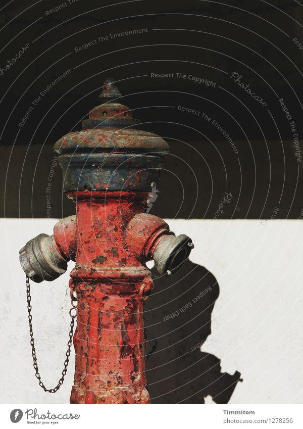 Alter Ego. Mauer Wand Hydrant Kette Anschluss Schatten Silhouette Metall stehen warten rot schwarz weiß Gefühle Sympathie deutlich unpersönlich Zuneigung