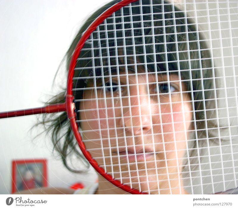 Gesicht einer jungen Frau versteckt sich hinter einem federballschläger. Wiederholung der Farbe rot. Sportmuffel. Unsportlich. Abwehr Federballschläger