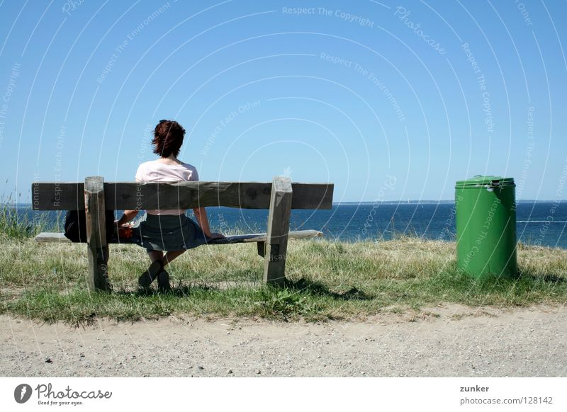 Weitblick Frau Holz Müllbehälter grün Meer Ferne Gras Einsamkeit Pause Außenaufnahme Konzentration Strand Küste Rücken Bank Wasser Himmel Schönes Wetter blau