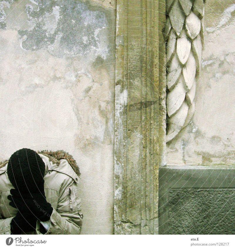 200 | beschämt Kerl Mann maskulin Körperhaltung Wand Mauer Mütze Handschuhe schwarz Jacke Winter kalt ungemütlich Muster Putz Kranz grün blamabel Quadrat Osten