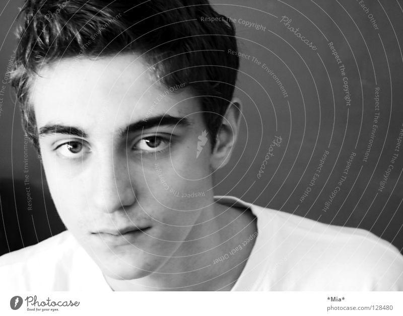 Junge mit weißem T-Shirt vor dunkler Wand Augenbraue Seite schwarz links Querformat Schwarzweißfoto Typ Gesicht Nase Mund Ohr Haare & Frisuren Blick geneigt