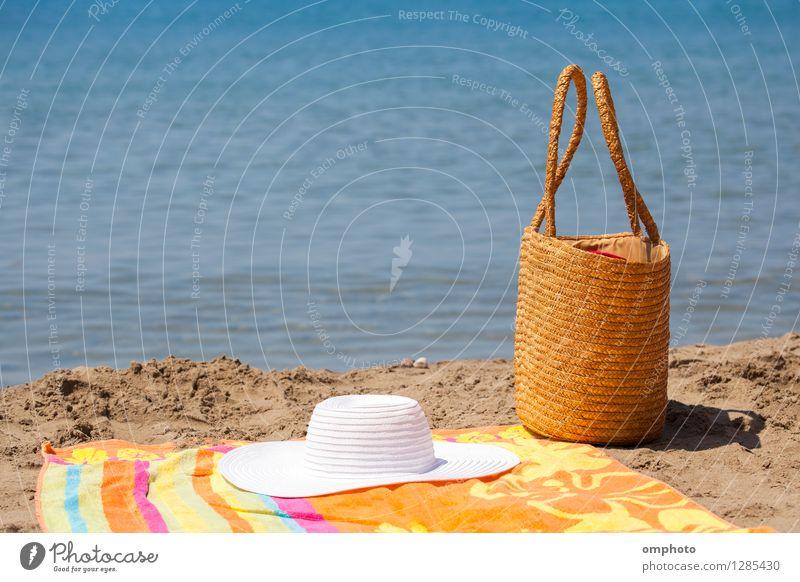 Mehrere Strandaccessoires, Tasche, Hut und farbiges Handtuch auf den Sand in der Nähe des Meerwassers gelegt Erholung Freizeit & Hobby Ferien & Urlaub & Reisen