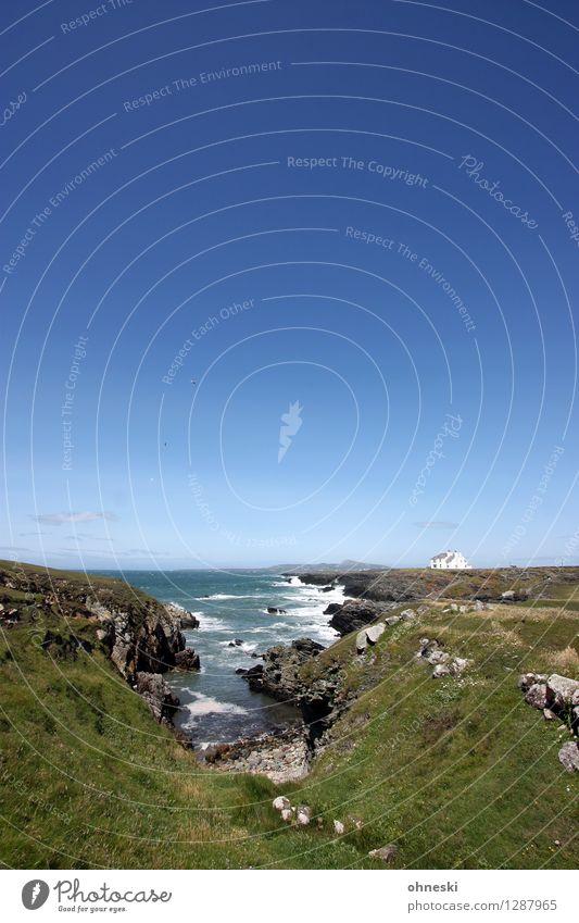 Haus am Meer Landschaft Schönes Wetter Hügel Felsen Wellen Küste Bucht Anglesey Wales Unendlichkeit wild blau Ferien & Urlaub & Reisen Freiheit ruhig Ferne