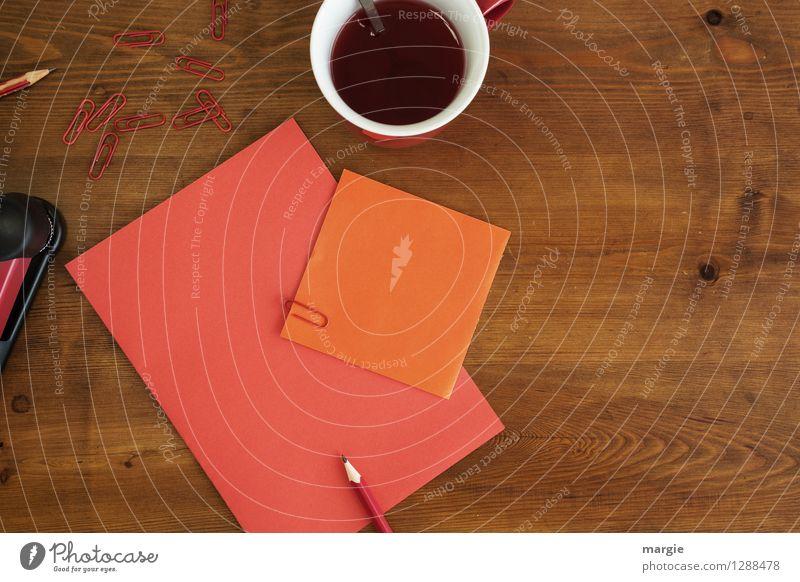 Rot oranges Büro: Zettel mit Bleistift, Büroklammern und eine Tasse roter Tee Heißgetränk Kaffee Löffel Schreibtisch Tisch Schule lernen Büroarbeit Business