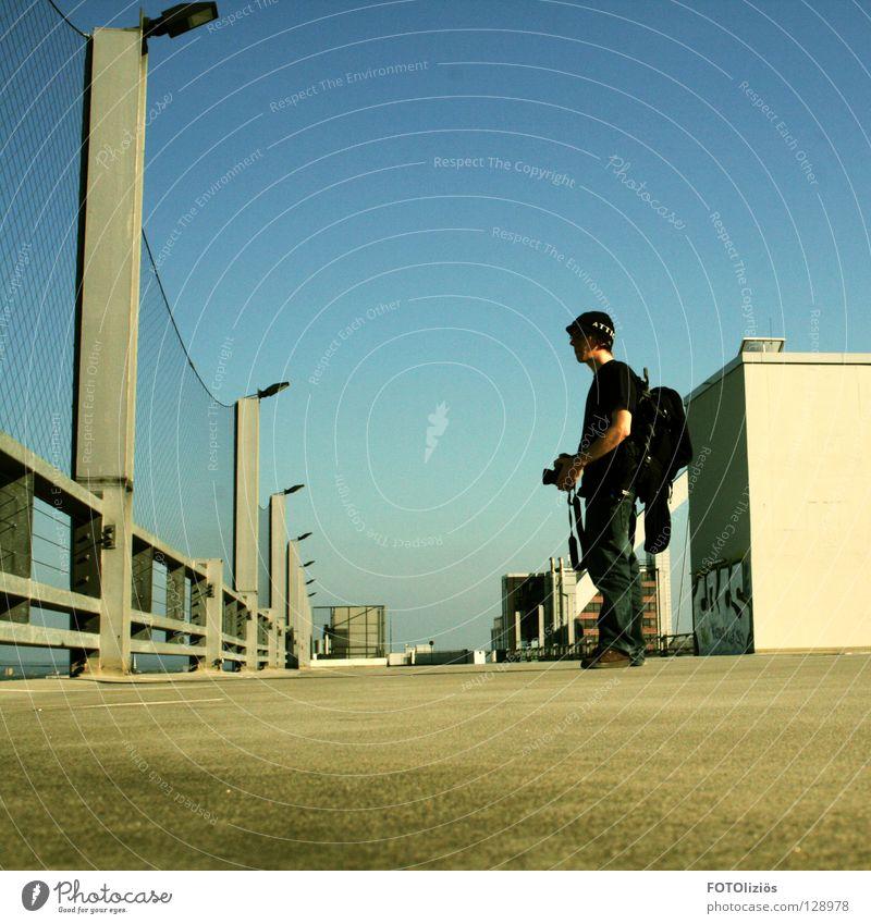 Fotopause Köln Mütze Fotografie Wand Asphalt Lampe Rucksack Paparazzo Dach köln dachparkplatz dachterasse parkplatz fotograf Fotokamera graffitti Bodenbelag
