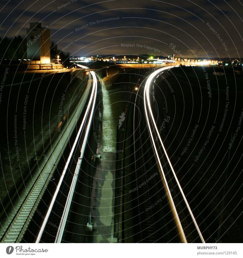 Züge in der Nacht Eisenbahn Gleise Langzeitbelichtung Stadt Silo Güterwaggon Güterzug Schnellzug Leuchtspur Licht Wolken Baum Lampe Horizont grau schwarz gelb