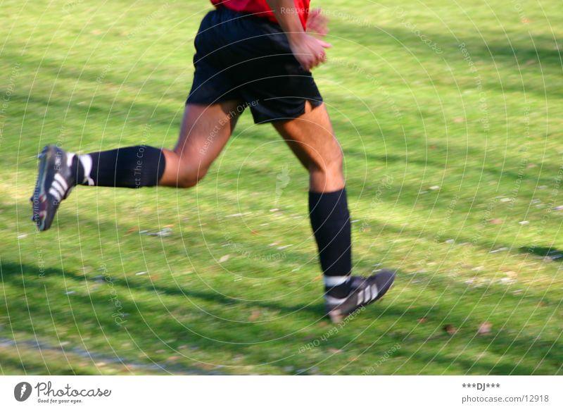 Lauf wenn du kannst! Mensch Mann Sport Spielen Gras Fuß Beine Fußball laufen Schönes Wetter Shorts verlieren Schuhe kürzen Fußballschuhe