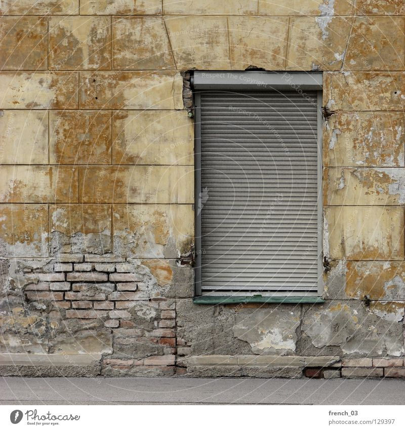 wohnst du noch? Haus Wand Mauer Fenster Rollladen gelb kaputt verrotten Backstein veraltet Gebäude beige Putz zerbröckelt geschlossen Unbewohnt Einsamkeit leer