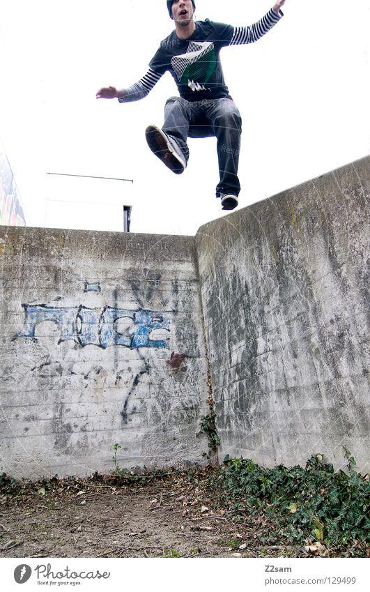 abwärts Mensch Mann Jugendliche Wand Graffiti springen Mauer Erde dreckig fliegen maskulin Beton Sträucher Coolness Niveau Jeanshose