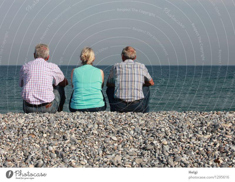Rückansicht  einer Seniorin und zwei Senioren, die auf Kies sitzen und aufs Meer schauen Ferien & Urlaub & Reisen Mensch maskulin feminin Frau Erwachsene Mann