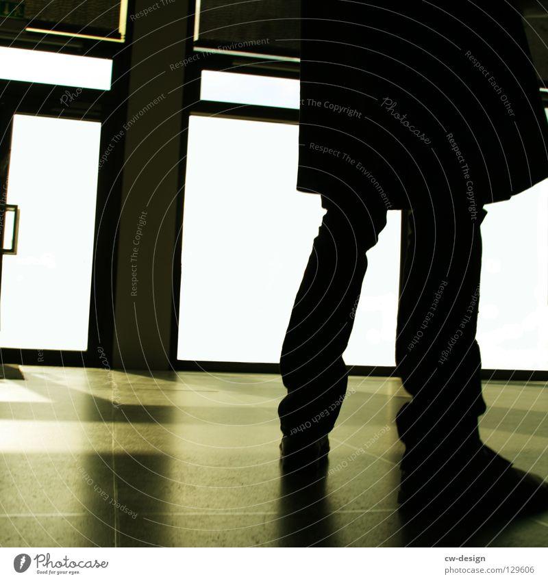 DEIN BILD WURDE LEIDER QUADRATISIERT dunkel schwarz weiß Licht Eingang Ausgang Mann Schuhe bodennah Mantel Hose Grauwert grau Bodenbelag Fuge Gebäude Fenster