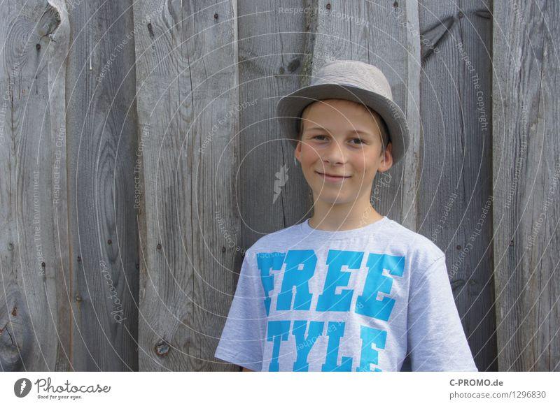 Junge mit Hut vor Holzzaun Mensch maskulin Kind 1 3-8 Jahre Kindheit 8-13 Jahre Mauer Wand T-Shirt Lächeln lachen frei Fröhlichkeit grau Coolness