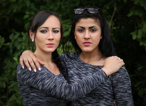 Nastya und Estila feminin 2 Mensch Park T-Shirt Schmuck Sonnenbrille schwarzhaarig langhaarig beobachten festhalten Blick warten stark selbstbewußt Coolness