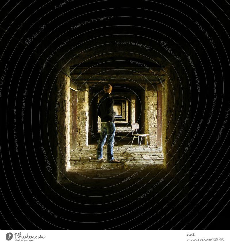 [i_] Kerl Mann maskulin Körperhaltung stehen dunkel Keller tief Licht Ferne Mauer Wand Verfall historisch Muster schwarz gelb Quadrat Sitzgelegenheit Hose