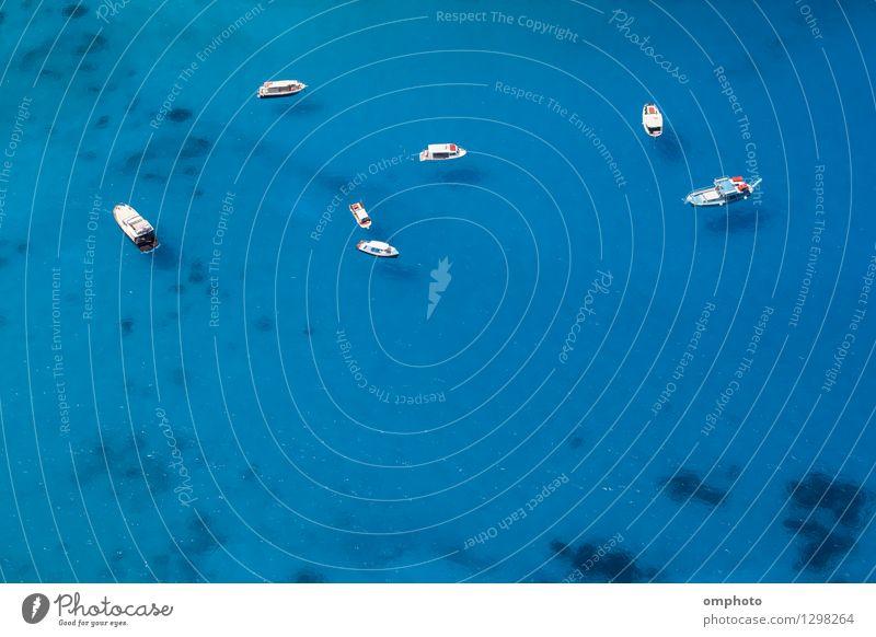 Luftaufnahme von mehreren Booten, die in einer Meeresbucht mit flachem, klarem, blauem Wasser vor Anker liegen. Das Wasser ist so sauber, dass man die Schatten der Boote auf dem Meeresboden sehen kann.