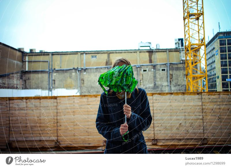 Anonymisierung mit Regenschirm Mensch Frau Jugendliche grün Junge Frau 18-30 Jahre Erwachsene feminin Mauer Angst blond Baustelle geheimnisvoll festhalten Zaun Regenschirm