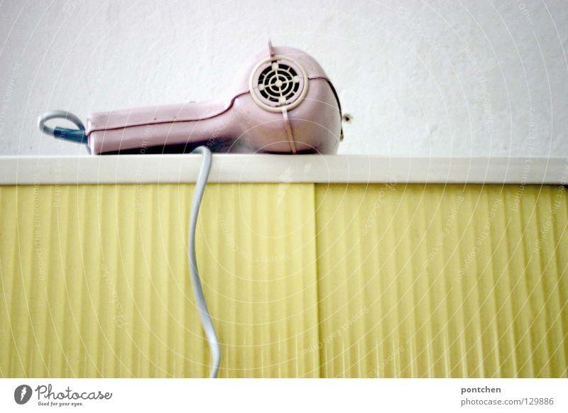 Pastellfarben. Ein rosa Föhn aus den 50ern liegt auf einem gelben badschrank. Vintage, rockabilly. Stil Design Haare & Frisuren Zufriedenheit Häusliches Leben