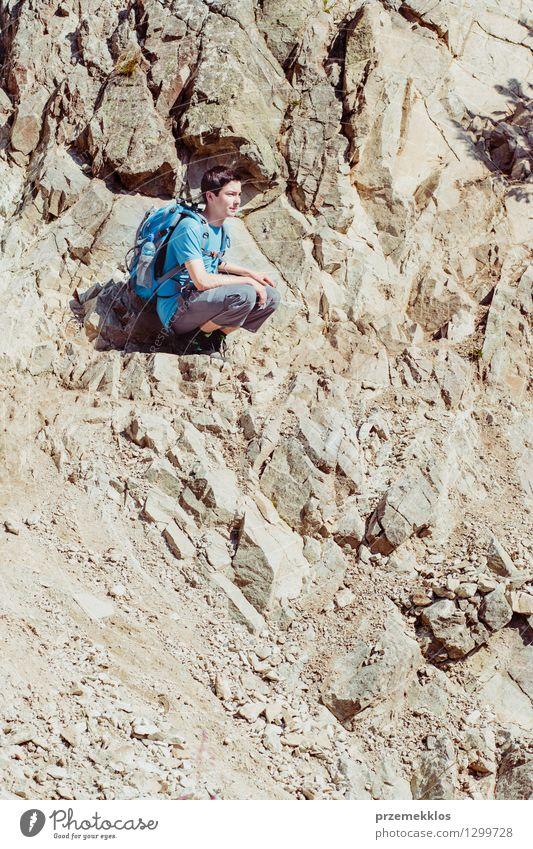 Junge, der auf dem felsigen Abhang sitzt Mensch Natur Ferien & Urlaub & Reisen Jugendliche Sommer Junger Mann Freude Berge u. Gebirge Felsen wandern 13-18 Jahre