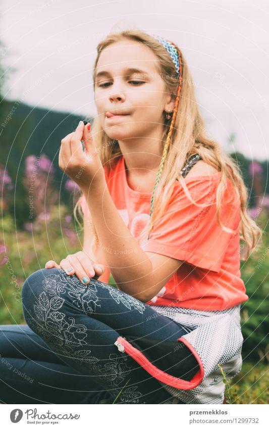 Mädchen, das Blaubeere hält Frucht Kind 1 Mensch 8-13 Jahre Kindheit blond lecker Freude Blaubeeren Verkostung Zunge Farbfoto Außenaufnahme Tag Porträt