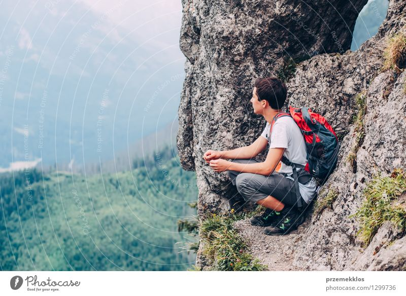 Junge, der auf den Felsen in den Bergen sitzt Mensch Kind Natur Ferien & Urlaub & Reisen Jugendliche Sommer Landschaft Junger Mann Freude Berge u. Gebirge