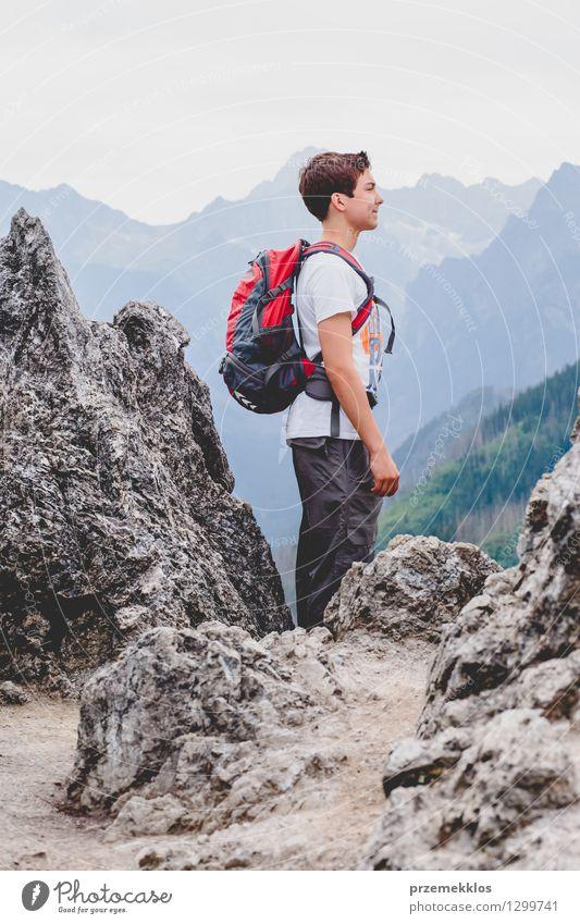Junge, der auf den Felsen in den Bergen steht Mensch Kind Natur Ferien & Urlaub & Reisen Jugendliche Sommer Landschaft Junger Mann Freude Berge u. Gebirge