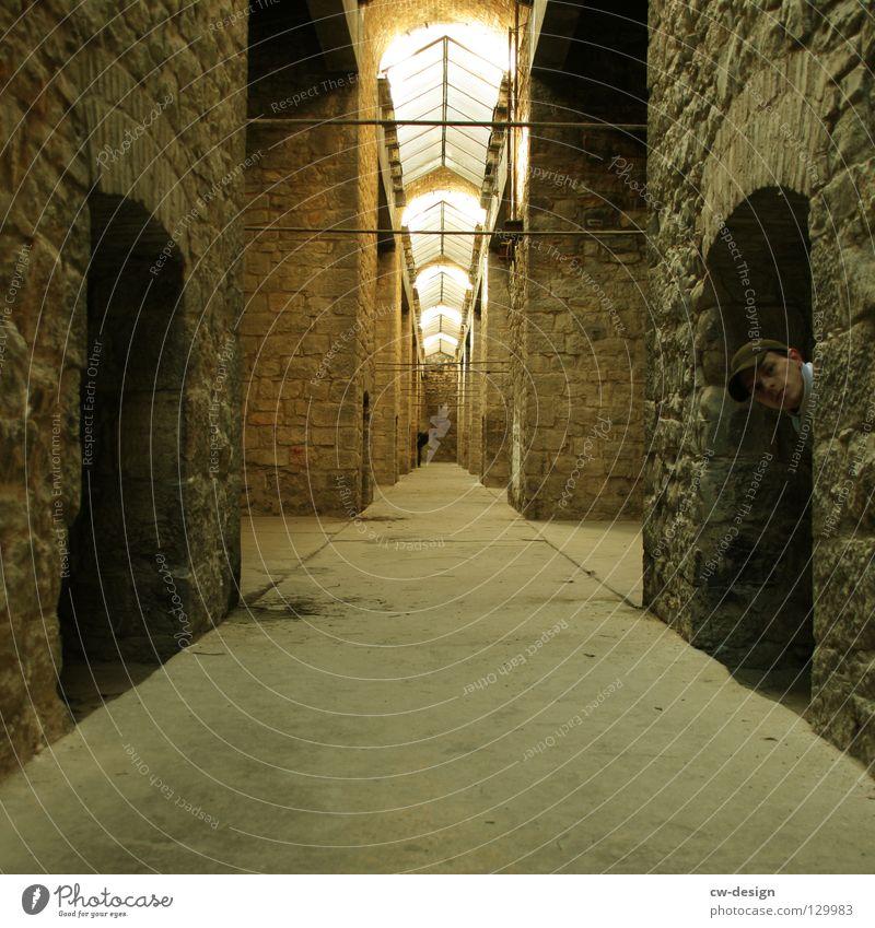 DAS VERSTECKSPIEL verstecken Versteck Gang Steinwand Oberlicht Arkaden Junger Mann Männerkopf Zentralperspektive Fluchtlinie Fluchtpunkt Innenaufnahme