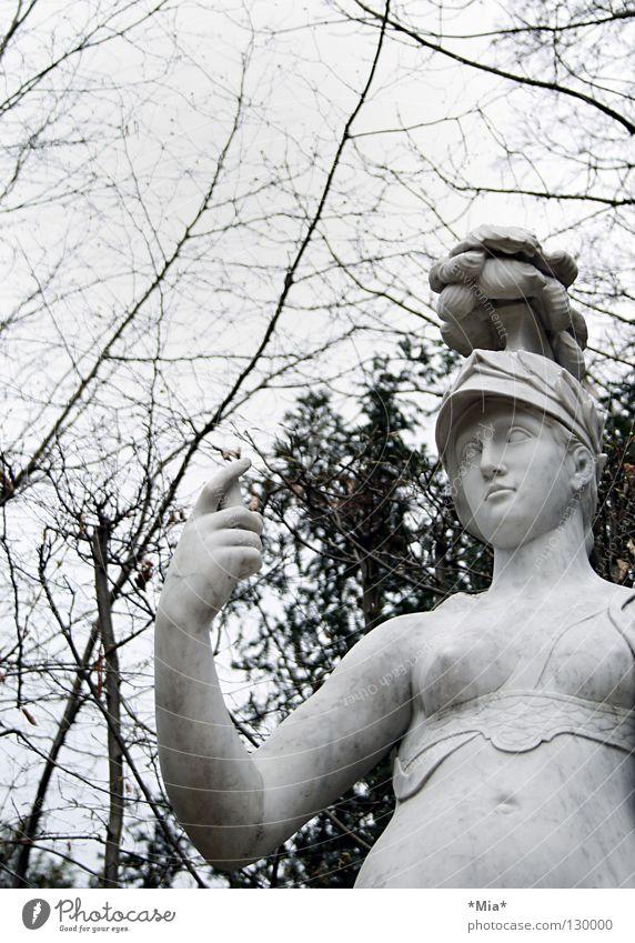 blind Statue Baum Geäst Sträucher dunkel grau schwarz weiß Frau haltend Helm Ast Zweig Himmel hell Blick Arme