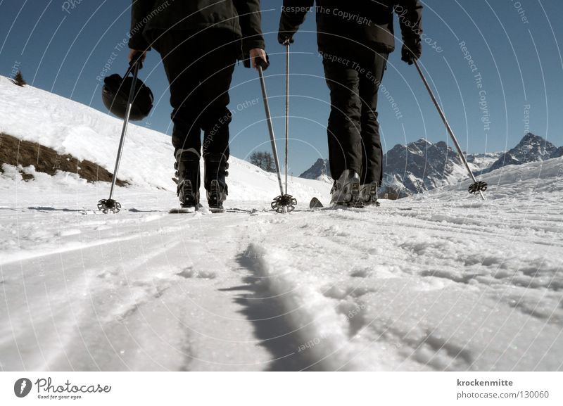black in white Winter Skifahren Skifahrer weiß Skier 2 Wintersport Winterurlaub kalt Skistöcke Helm Bergkette Froschperspektive schwarz Schneeanzug anstrengen