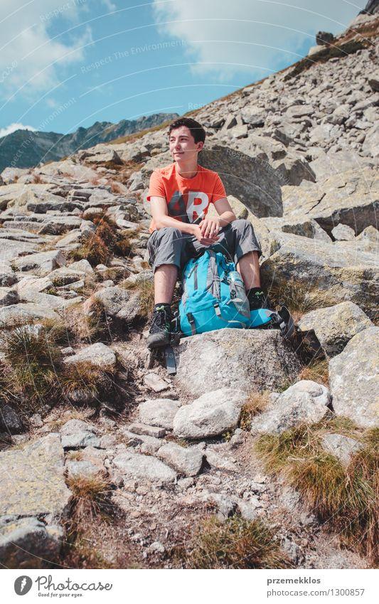 Junge, der auf einem Felsen in den Bergen stillsteht Lifestyle Ferien & Urlaub & Reisen Ausflug Abenteuer Freiheit Sommer Berge u. Gebirge wandern Junger Mann
