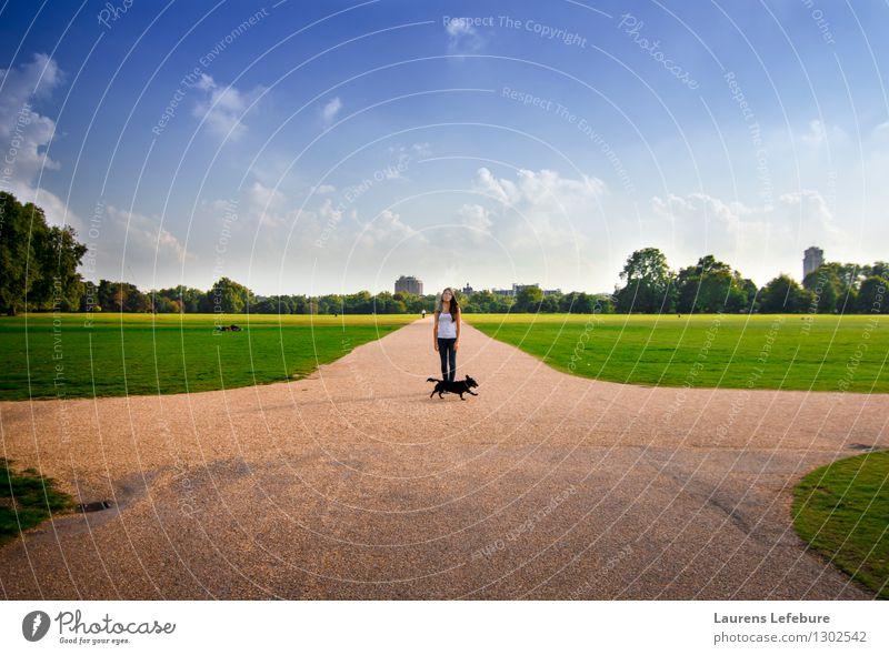 Junge Frau, die in einem London-Park steht. Mensch Hund Himmel Ferien & Urlaub & Reisen Jugendliche blau schön Sommer Baum Landschaft Wolken Tier 18-30 Jahre