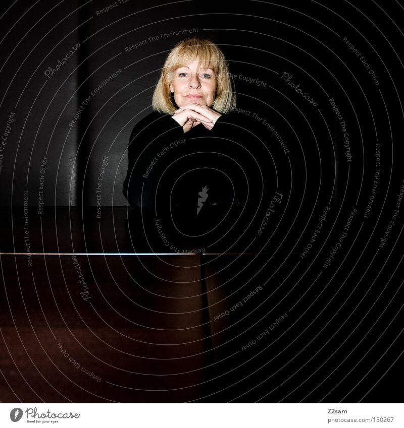 zufrieden Zufriedenheit Erfahrung Frau blond Porträt frontal Hand Mensch feminin schwarz Leder Tisch glänzend einfach Stil alt Dame Gesicht face Auge Anschnitt