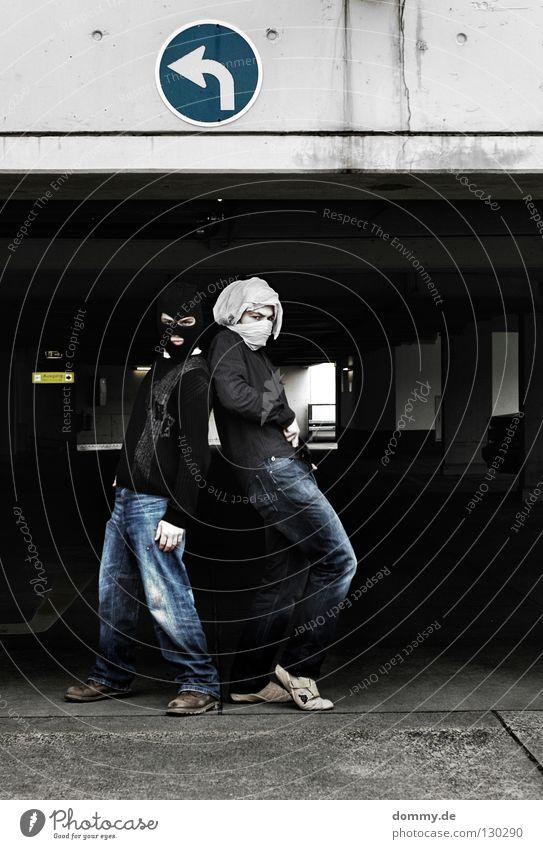 B&T | 01 Mann Kerl stehen Hose Pullover Hemd verpackt Turban weiß schwarz Turnschuh parken Parkhaus Parkplatz Parkdeck dunkel links rechts Körperhaltung