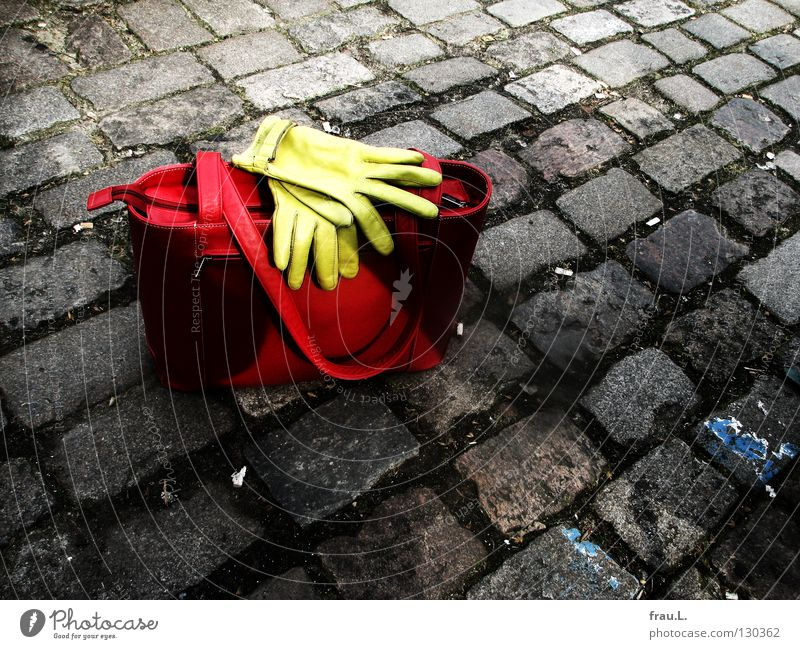 abgestellt Tasche Handschuhe rot grün Leder Platz stehen Körperhaltung Dinge Bekleidung Verkehrswege Kopfsteinplaster Straße liegen warten Ledertasche